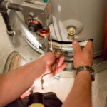 Plumber performing maintenance on a water heater in a West Chester home