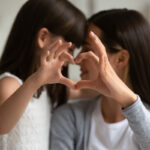 Mom with daughter with hands forming a heart